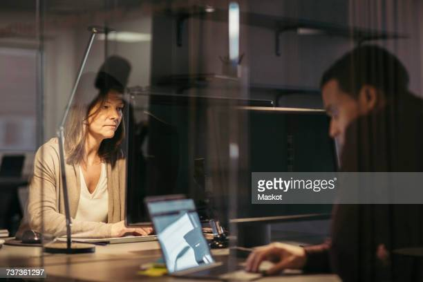 Business colleagues using technology while working late at office