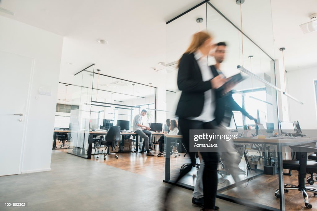Business colleagues walking and talking : Stock Photo