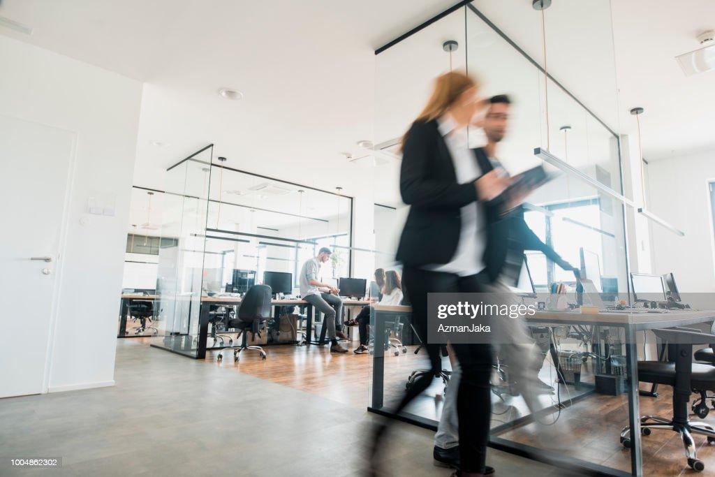Geschäftskollegen gehen und sprechen : Stock-Foto