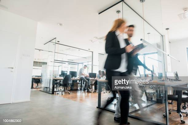 collega's lopend en pratend - business stockfoto's en -beelden
