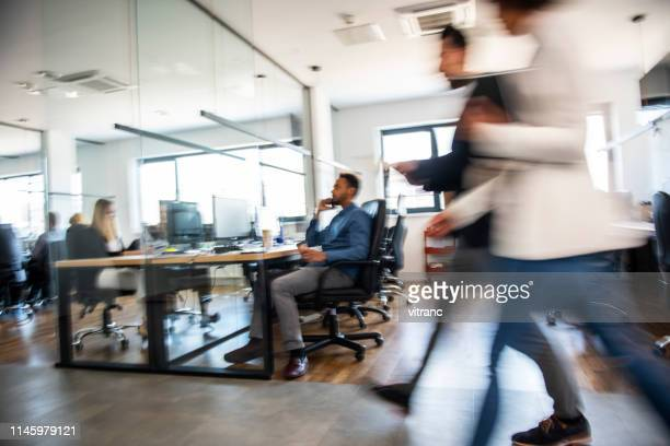 business colleagues walking and talking - design studio stock pictures, royalty-free photos & images