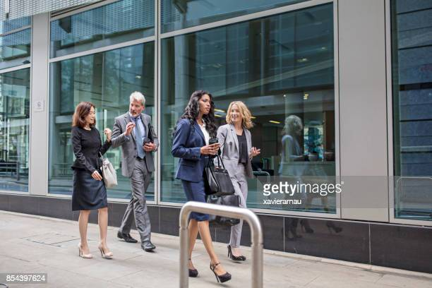 Business colleagues walking by modern building
