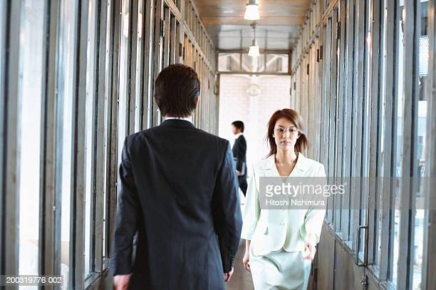 Business colleagues walking in corridor