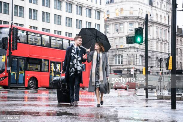 business colleagues walking in london street with umbrella and suitcase - wheeled luggage stock photos and pictures