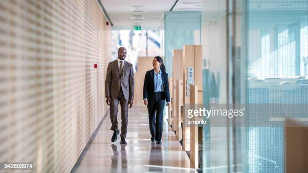 business colleagues walking in office - pant suit stock pictures, royalty-free photos & images