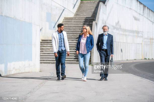 business colleagues walking in sunny urban location - approaching stock pictures, royalty-free photos & images