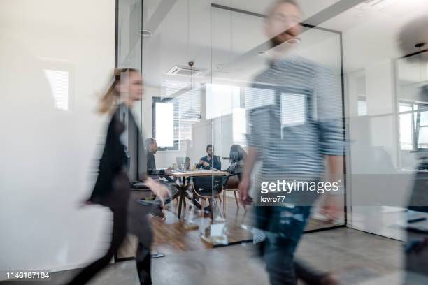 business colleagues walking in the office - immagine mossa foto e immagini stock