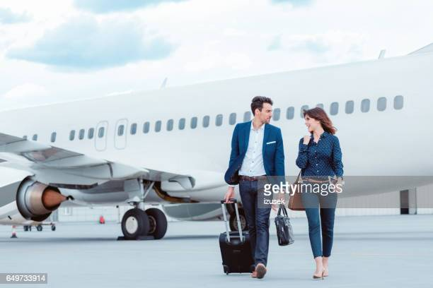 Business colleagues walking on tramac in front of airplane.