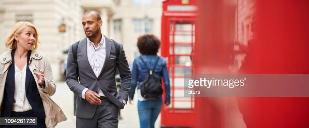 business colleagues walking through uk street - red suit stock pictures, royalty-free photos & images