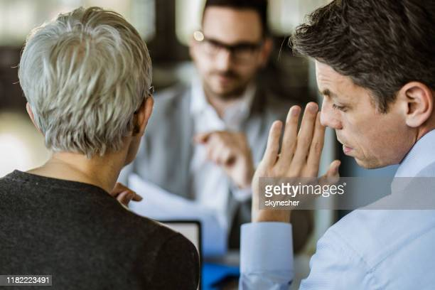 business colleagues whispering on a meeting in the office. - gossip stock pictures, royalty-free photos & images