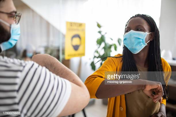business colleagues with face masks greeting with elbow bump at modern office - elbow bump stock pictures, royalty-free photos & images