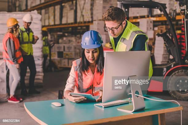 Kollegen arbeiten mit Tablet-Computer im Lager