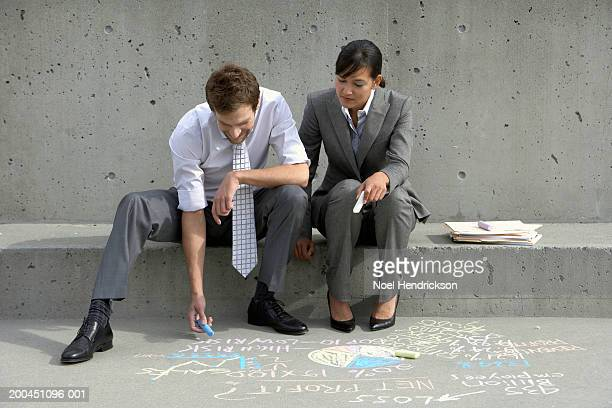 Business colleauges, man writing on sidewalk