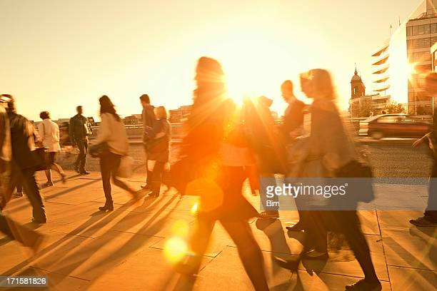business commuters walking home after work, sunset backlit, blurred motion - onderweg stockfoto's en -beelden