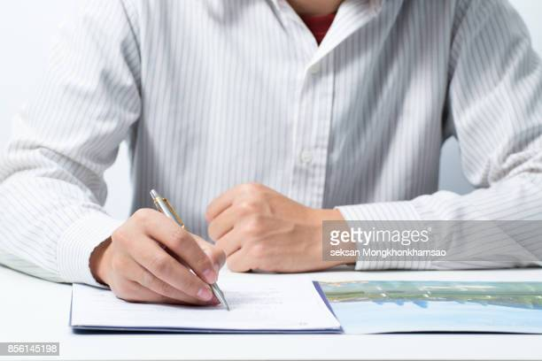 Business concept: businessman signs a contract. Holding pen in hand.
