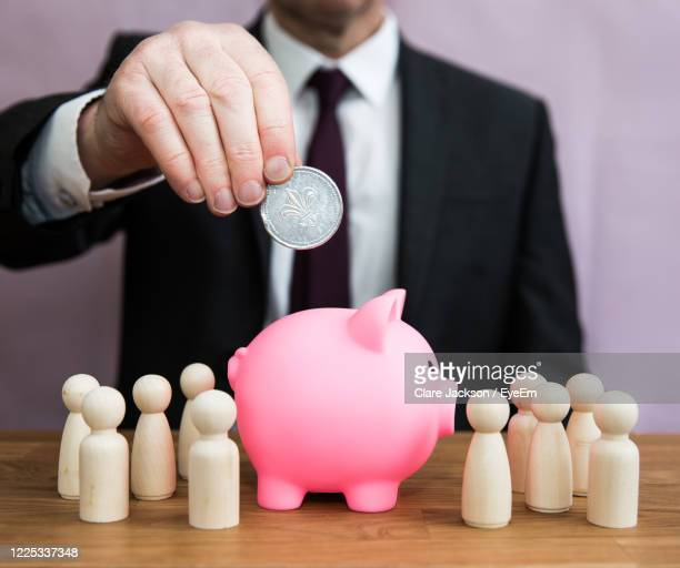 a business concept of a man paying into an employee salary, pension, tax, bonus or incentive scheme - percentage sign stock pictures, royalty-free photos & images