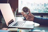 Business concepts with businessman holding clock on computer laptop.For investment analysis,Waiting to sucess