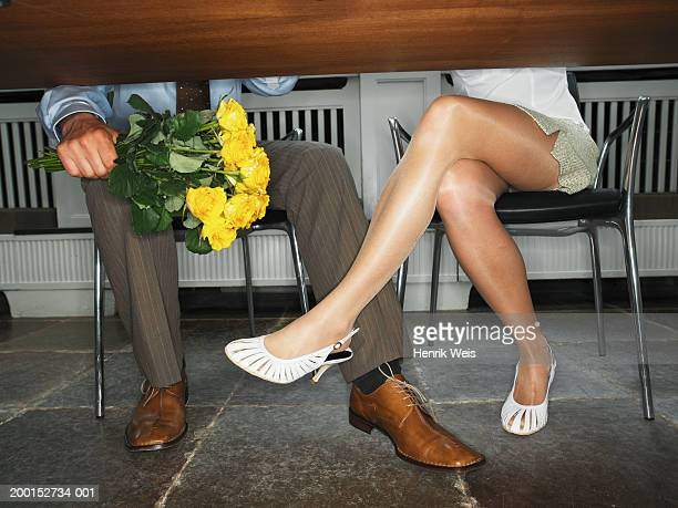 Business couple at desk, man holding bunch of roses, low section