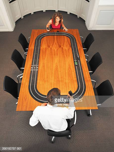 Business couple at desk playing with toy racing track, elevated view