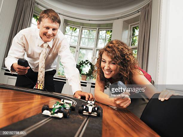 Business couple at desk playing with toy racing track, smiling