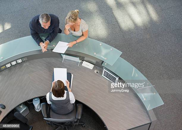 business couple at hotel reception - receptionist stock pictures, royalty-free photos & images