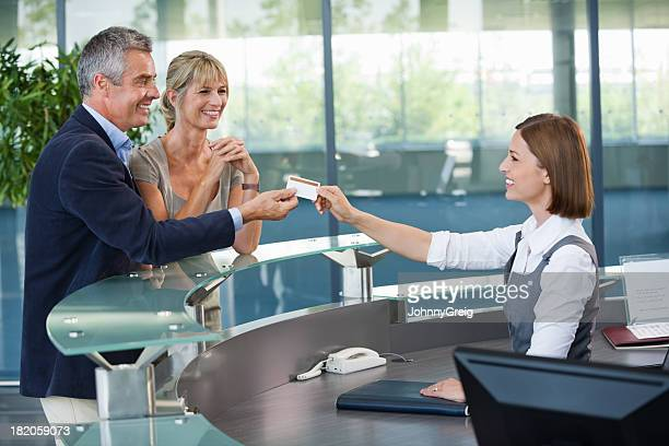 business couple collecting room access card - bezoek stockfoto's en -beelden