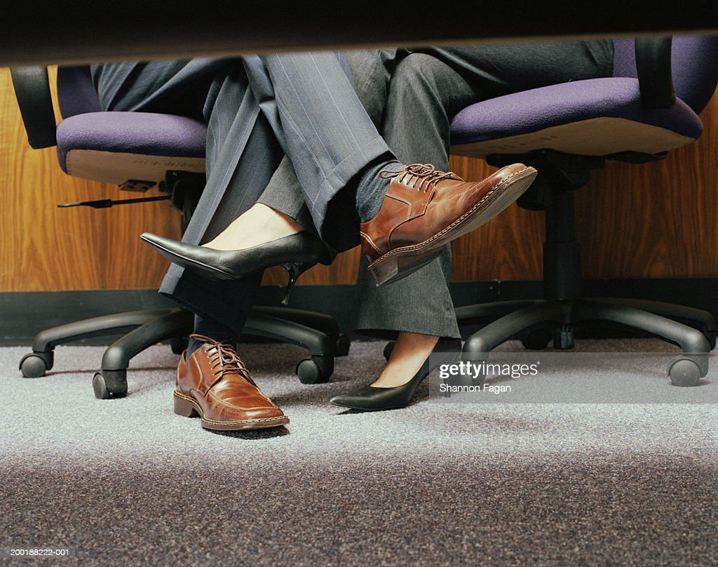 Business Crossing Legs Under Table Low Section Stock Photo
