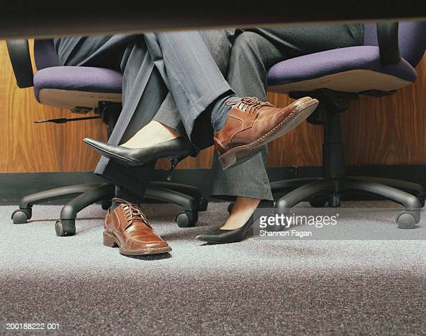 business couple crossing legs under table, low section - playing footsie stock photos and pictures