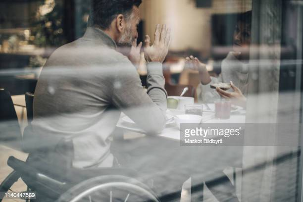 Business couple discussing while having breakfast at table in restaurant seen through window glass