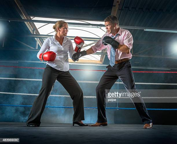 Business couple fighting in smokey boxing ring