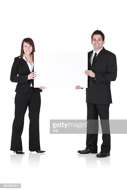 Business couple holding a placard