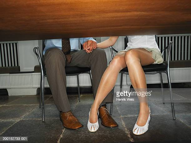 Business couple holding hands under desk, low section