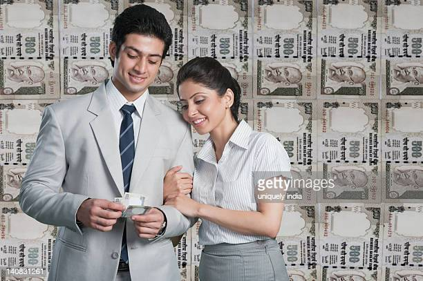 Business couple in front of a background of Indian currency notes