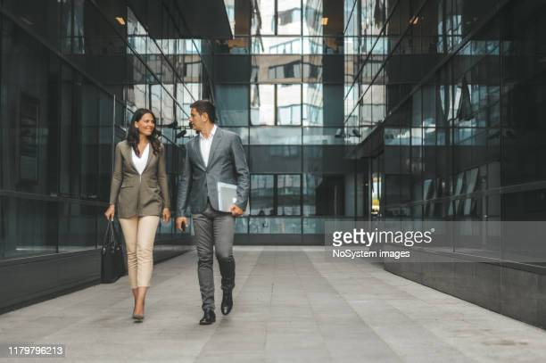 business couple in front of the office building - finance stock pictures, royalty-free photos & images