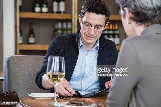 Business couple in restaurant paying with credit card