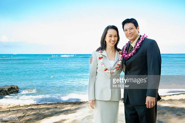 business couple in suits on beach with leis - lei day hawaii stock pictures, royalty-free photos & images