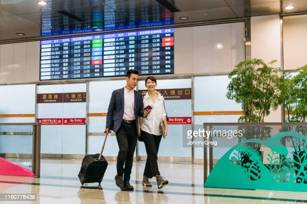 business couple passing arrivals board in airport - taipei stock pictures, royalty-free photos & images