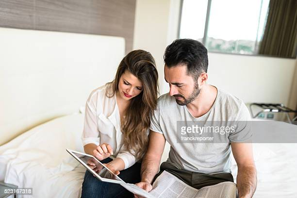 business couple reading newspaper on bedroom