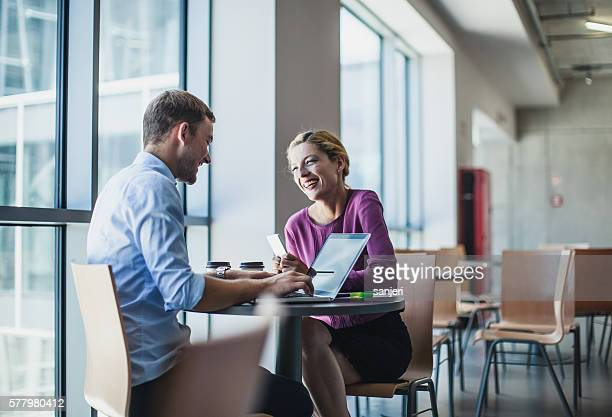 Business Couple Sitting at the Table and Using Portable Devices