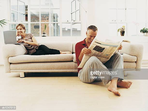 Business Couple Sitting in a Living Room Apartment Reading the Newsapaper and Using a Laptop