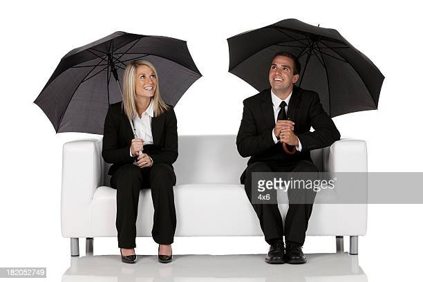 Business couple sitting on a couch under umbrellas