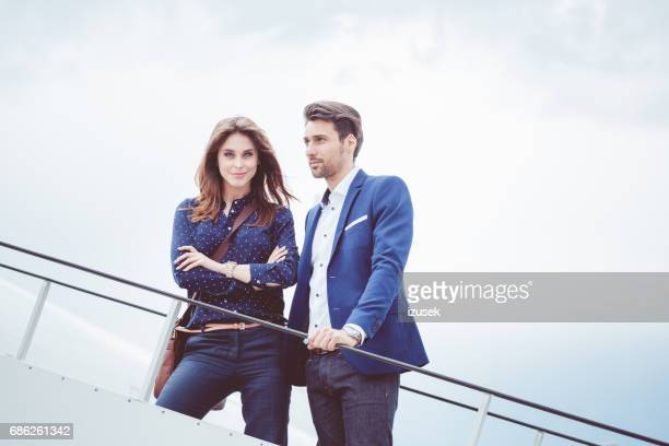 Business couple standing on the airplane staircase