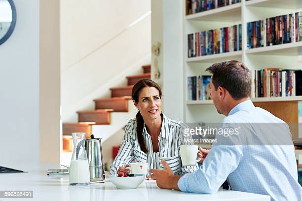 Business couple talking while having coffee