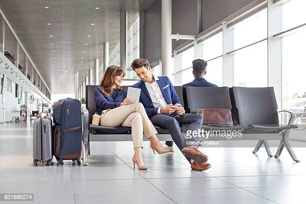 business couple waiting for flight at airport lounge - gate stock pictures, royalty-free photos & images