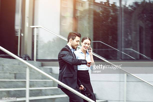 Business Couple Walking Down the Stairs