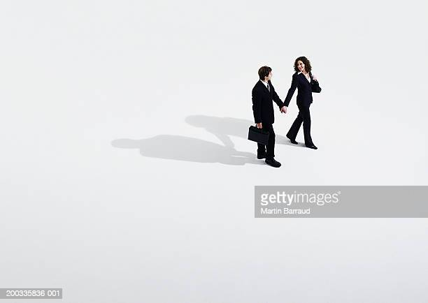 Business couple walking holding hands, elevated view