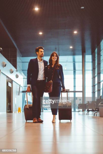 Business couple walking together at airport terminal