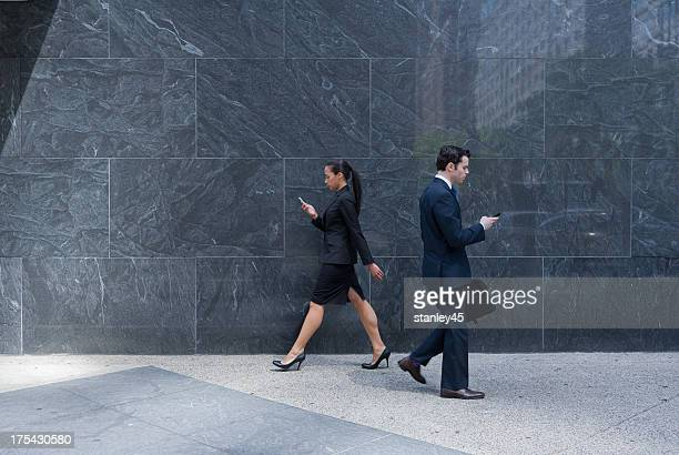 Business couple with cell phones  walking on a city sidewalk