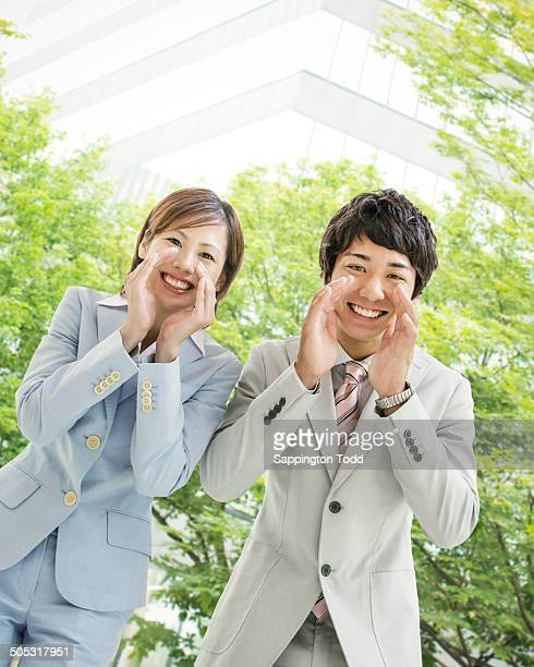 Business Couple With Cupped Hands Near Mouth