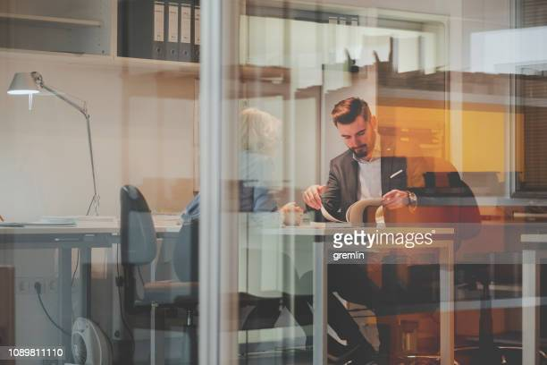 business couple working in the office - glass magazine stock photos and pictures